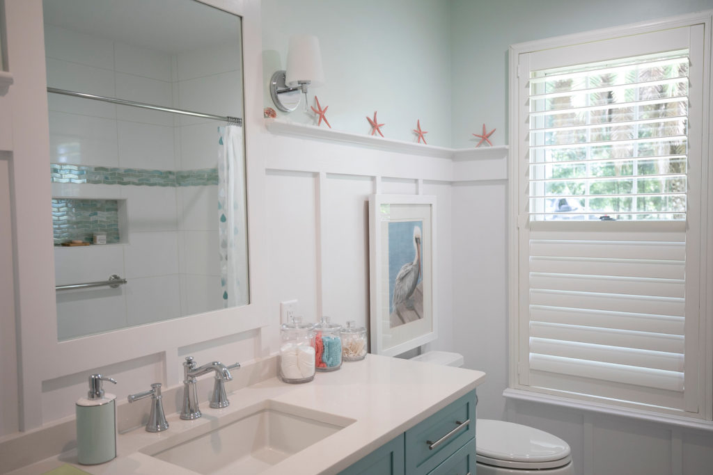 Coastal bathroom with white wall paneling, light blue walls, and modern fixtures.