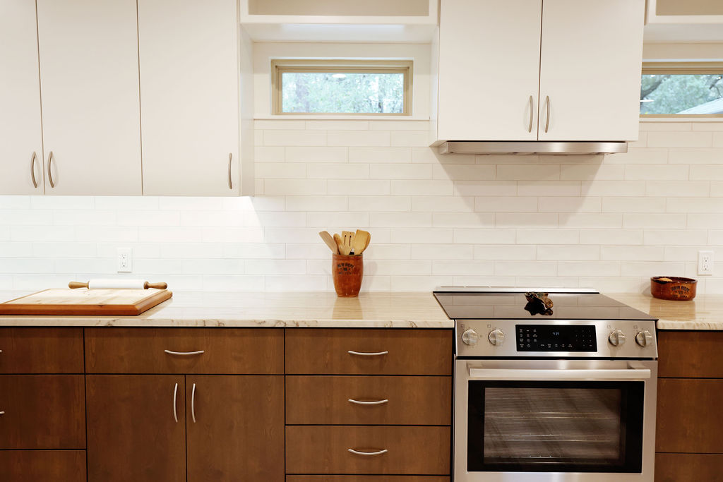 Residential kitchen with white tile and wood cabinets