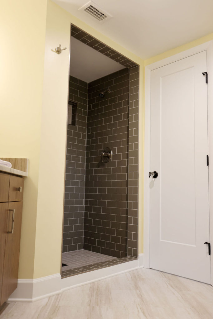Bathroom with pale yellow walls and a grey tiled shower